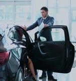 Młoda dama wybiera nowego samochód dla kupować w przedstawicielstwo handlowe sklepie Zdjęcia Stock
