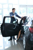 Młoda dama wybiera nowego samochód dla kupować w przedstawicielstwo handlowe sklepie Fotografia Royalty Free
