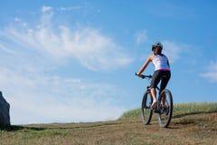 Młoda dama z bicyklem na wiosny łące Zdjęcia Royalty Free