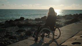 Młoda dama z chorobą kręgosłup siedzi w wózku inwalidzkim na wybrzeżu morze zbiory