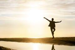 Młoda dancingowej dziewczyny sylwetka w sunbeam przy zmierzchem na plaży Zdjęcie Royalty Free