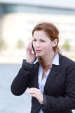 Młoda dorosła biznesowa kobieta opowiada w mądrze telefonie Zdjęcie Stock
