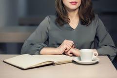 Młoda dorosła kobieta kawową przerwę w kawiarni, writing notatkach w i; dzienniczku lub notepad Zdjęcia Royalty Free