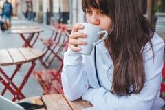 Młoda dorosła kobieta pije herbaty przy outdoors kawiarnią zdjęcia stock