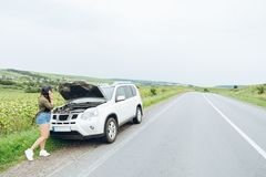 Młoda dorosła kobieta stoi blisko łamanego samochodu na autostradzie i talkin fotografia stock