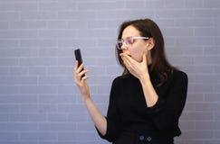 Młoda dorosła kobieta używa telefonu komórkowego okładkowego usta z ręką szokował z wstydem dla błędu fotografia royalty free