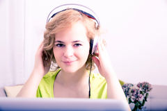 Młoda dorosła kobieta z hełmofonami przed laptopem zdjęcia royalty free