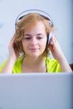 Młoda dorosła kobieta z hełmofonami przed laptopem zdjęcia stock