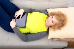 Młoda dorosła kobieta z pastylka pecetem na kanapie zdjęcia stock