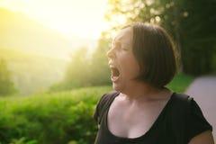 Młoda dorosła kobieta ziewa outdoors w ranku fotografia stock