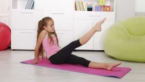 Młoda dziewczyna ćwiczy w domu - nogi szkolenie zbiory wideo
