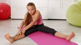 Młoda dziewczyna ćwiczy w domu - rozciąganie zbiory