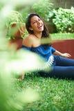 Młoda dziewczyna śmiech na trawie zdjęcia stock