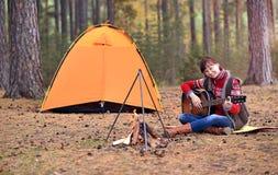 Młoda dziewczyna bawić się gitarę w lesie zdjęcie stock