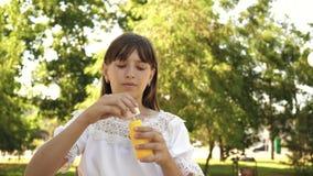 Młoda dziewczyna bawić się w dmuchanie bąblach i parku w kamera obiektyw swobodny ruch Piękny dziewczyny dmuchania mydło zbiory