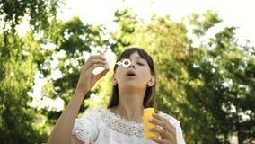 Młoda dziewczyna bawić się w dmuchanie bąblach i parku w kamera obiektyw swobodny ruch Piękny dziewczyny dmuchania mydło zdjęcie wideo