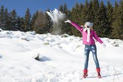 Młoda dziewczyna bawić się z śniegiem w zimie zdjęcie stock