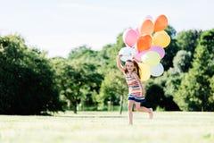 Młoda dziewczyna bieg na trawy polu z balonami obraz stock