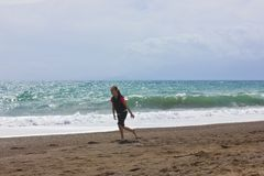 Młoda dziewczyna biega i skacze na plaży blisko błękitnego morza obraz stock