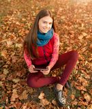 Młoda dziewczyna bierze obrazkowi cyfrowego pastylka komputer osobistego w jesień parku Zdjęcia Stock