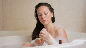 Młoda dziewczyna bierze skąpanie z pianą i płuczkowego włosy z szamponem Wielki bielu skąpanie i mała butelka szampon przy zbiory