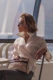 Młoda dziewczyna biznesmena obsiadanie przy cukiernianym stołem z okularami przeciwsłonecznymi na tle okno nowożytny centrum bizne Obraz Stock
