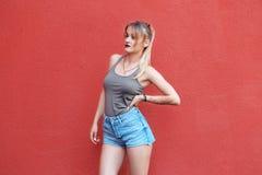 Młoda dziewczyna blisko czerwonej ściany Zdjęcie Royalty Free