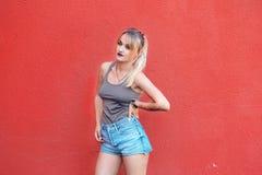 Młoda dziewczyna blisko czerwonej ściany Obrazy Stock