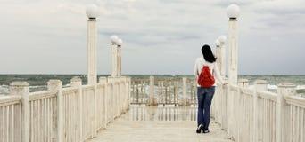 Młoda dziewczyna & x28; brunette& x29; w cajgach z czerwień plecaka pozycją na t Fotografia Royalty Free