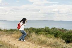 Młoda dziewczyna & x28; brunette& x29; w cajgach z czerwonym plecakiem z kamerą Obrazy Royalty Free