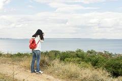 Młoda dziewczyna & x28; brunette& x29; w cajgach z czerwonym plecakiem z kamerą Fotografia Royalty Free