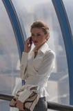 Młoda dziewczyna businessmantalking na telefonie komórkowym na tle okno nowożytny centrum biznesu Fotografia Stock