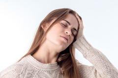 Młoda dziewczyna chwytów ręka za jego głową odizolowywającą na białym tle zdjęcia stock