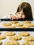 Młoda dziewczyna chwyta ciastka od wypiekowej tacy fotografia stock