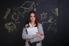 Młoda dziewczyna, chwyty falcówka papiery stanowczo w rękach, stoi obok deski z obrazkiem nauki fotografia royalty free