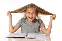 Młoda dziewczyna ciągnie jej włosy w stresie nad pracującym edukaci pojęciem i obraz stock