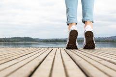 Młoda dziewczyna cieki z butami i niebieskimi dżinsami na drewnianym molu tiptoed Obraz Stock