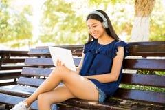 Młoda dziewczyna cieszy się dopatrywanie film na cyfrowej pastylce zdjęcia stock