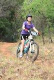Młoda dziewczyna cieszy się outdoors przejażdżkę przy rower górski rasą Obraz Royalty Free