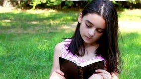 Młoda dziewczyna czyta Świętą biblię. zbiory wideo