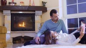 Młoda dziewczyna czyta książkę dla jej męża kłaść na jego kolanach przy podłoga zbiory wideo