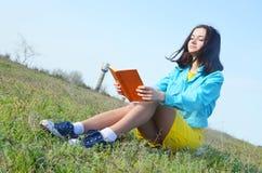 Młoda dziewczyna czyta książkę na polu w lecie obrazy stock