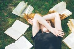 Młoda dziewczyna czyta książkę podczas gdy kłamający w trawie Dziewczyna wśród książek w lato ogródzie Fotografia Stock