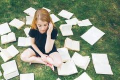 Młoda dziewczyna czyta książkę podczas gdy kłamający w trawie Dziewczyna wśród książek w lato ogródzie obrazy stock