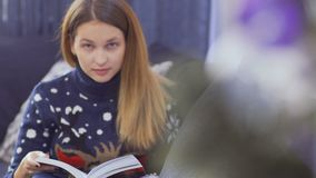 Młoda dziewczyna czyta książkowej pobliskiej choinki zdjęcie wideo