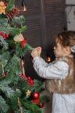 Młoda dziewczyna dekoruje choinki czerwoną piłką i inny bawi się Obraz Stock