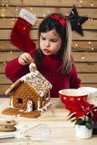 Młoda dziewczyna dekoruje piernikowego dom fotografia royalty free