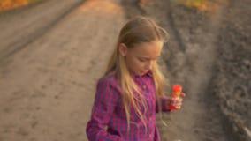Młoda dziewczyna dmucha mydlanych bąble outdoors Młodej dziewczyny wiejska droga Zamyka w górę unfocused swobodny ruch zdjęcie wideo