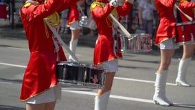 Młoda dziewczyna dobosz w czerwieni przy paradą W górę żeńskich ręk dobosze puka w bębenie ich kije zbiory