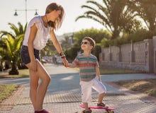 Młoda dziewczyna i śliczny dzieciak z a jeździć na deskorolce plenerowego Obraz Stock